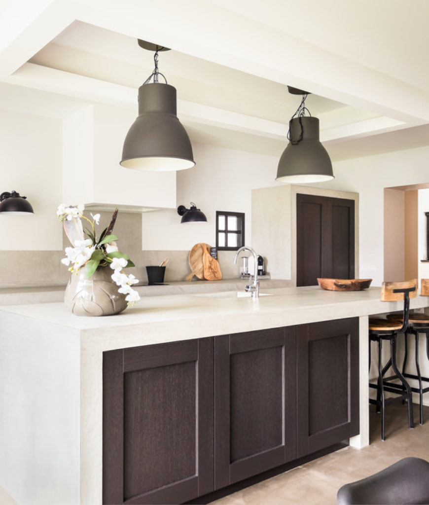 White kitchen with dark wood island that has white surface that waterfalls down the ends.