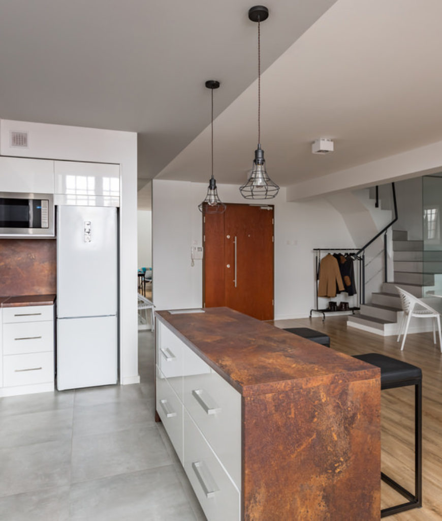 Copper color waterfall island in L-shaped kitchen.