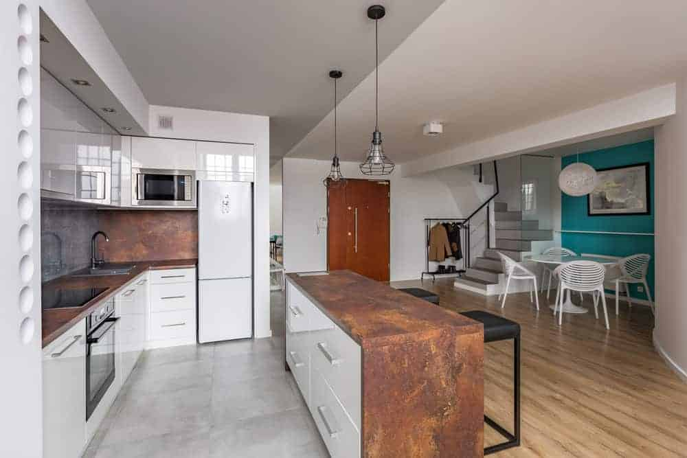 This white kitchen with gray tiles flooring offer bronze-like counters. The narrow center island is lighted by a couple of pendant lights.