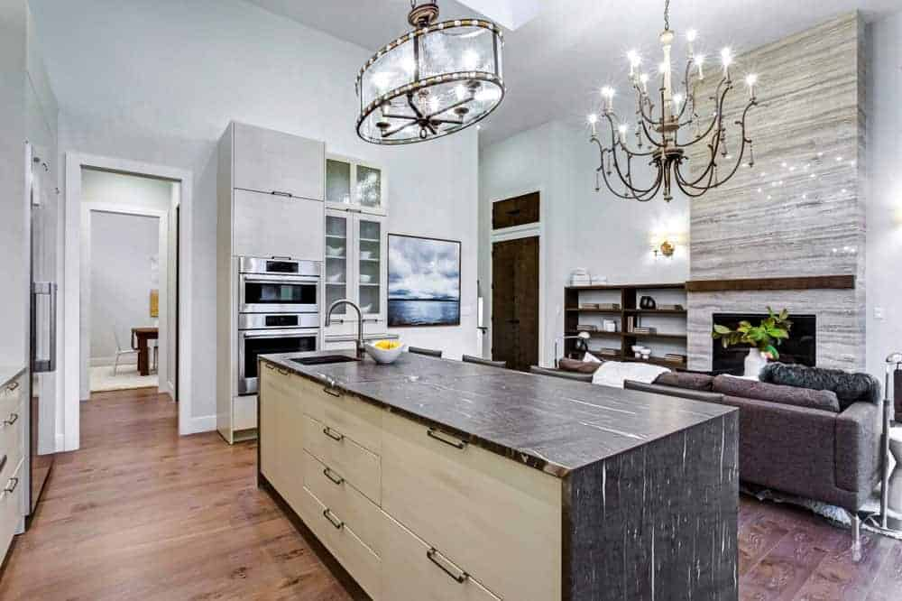 Elegant looking Mediterranean kitchen featuring a hardwood flooring and a large center island lighted by a chandeliers. The countertop of the center island looks stylish.