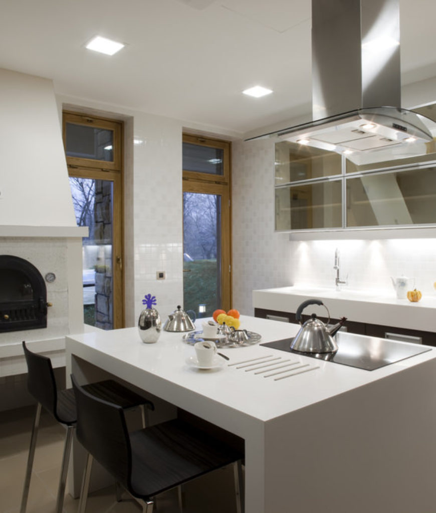 White kitchen island with waterfall surface in contemporary kitchen with recessed lighting.