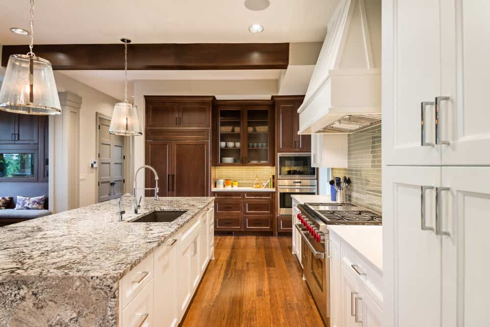 Contemporary L-shaped kitchen with a marble countertop island, white and brown wooden cabinets, hardwood floors, and a combination of recessed and pendant lights.