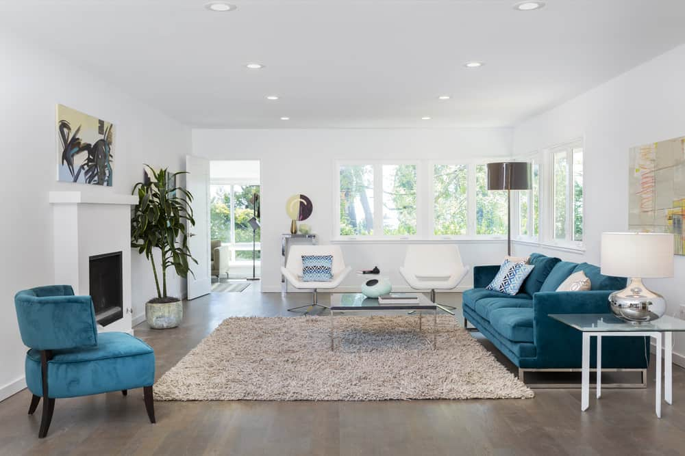 White formal living room with blue furniture and hardwood flooring.