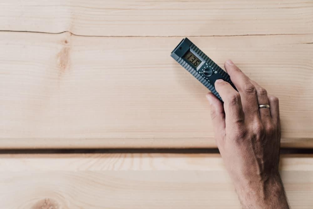 Hand holding a wood moisture meter on hardwood floor.