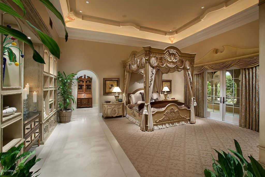 Luxurious master bedroom with large canopy bed under tray ceiling.