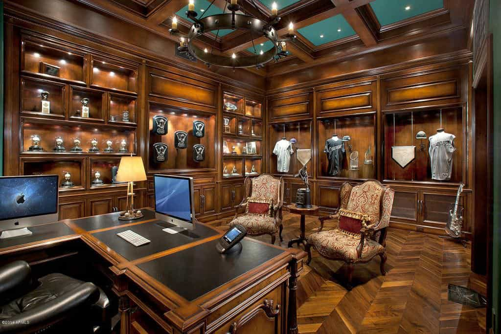 Luxurious home office with expensive wood paneling, flooring and coffered ceiling.