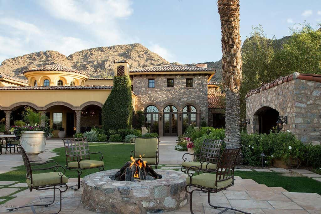 Backyard of mansion with large patio with fire pit.