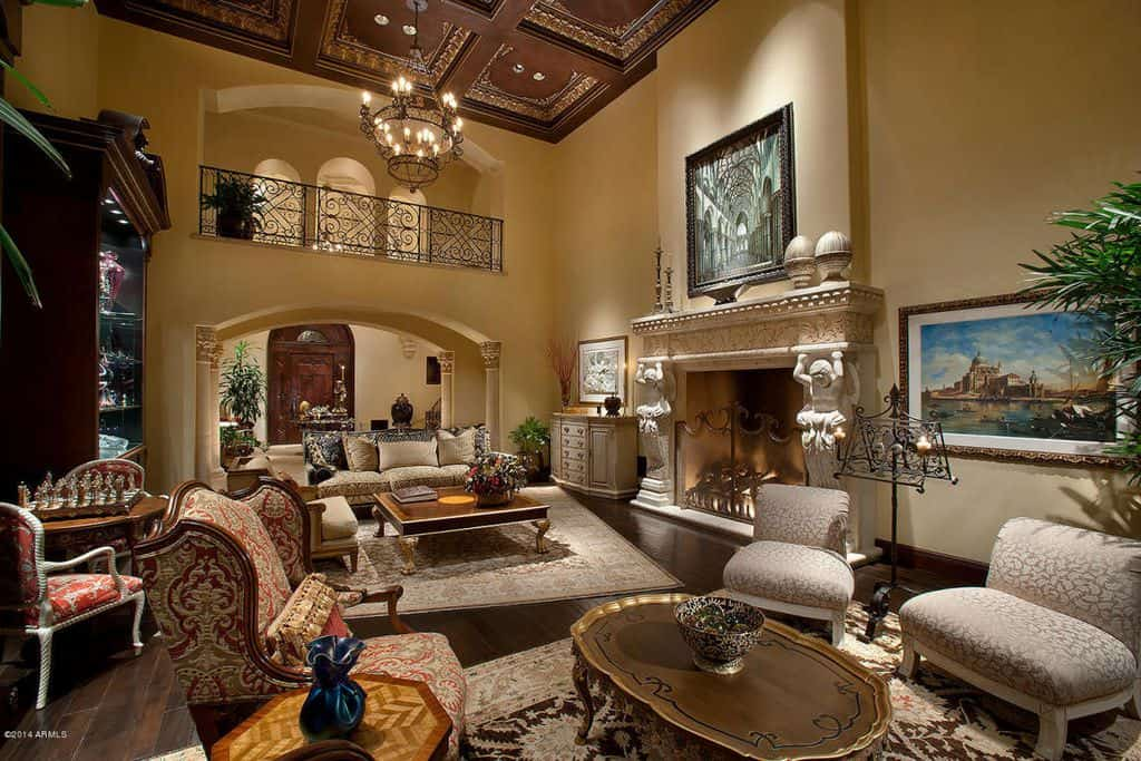 Two story luxury living room with beige walls, chandelier and earth tones throughout.