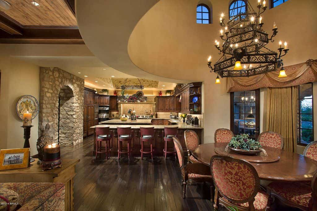 spacious southwestern style kitchen with beige ceiling, wood flooring and brick archway.