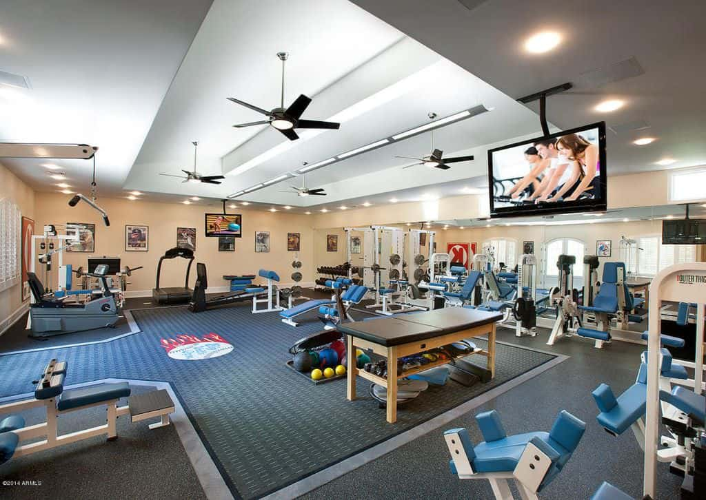 Huge home gym with ceiling fans and loads of exercise equipment.