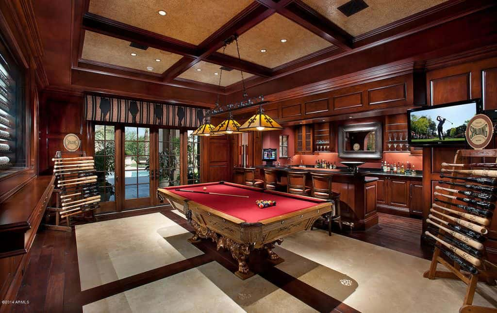 This home features a game room boasting an elegant style billiards pool and a classy bar area.