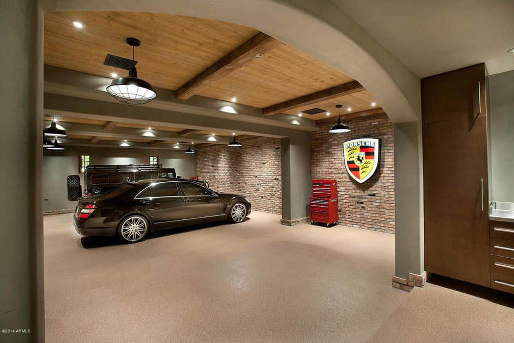 Large custom luxury garage interior with wood-beamed ceiling and brick wall.