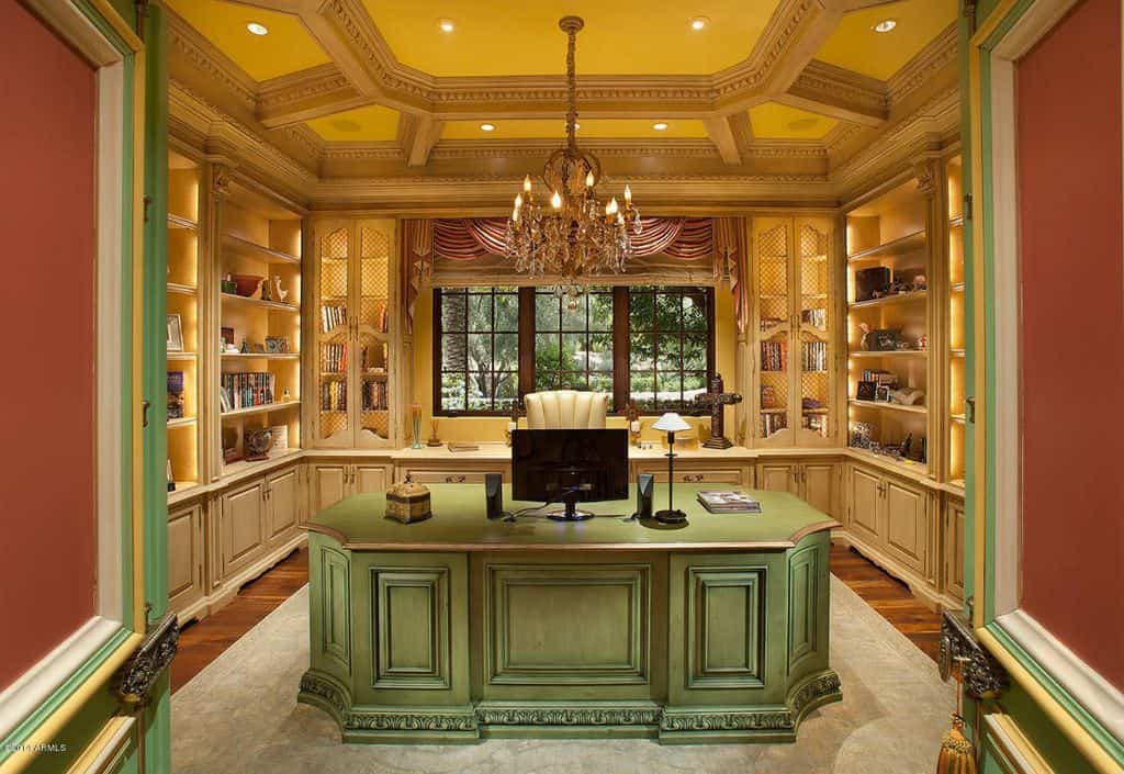 Elegant home office with custom green wood desk and built in storage.