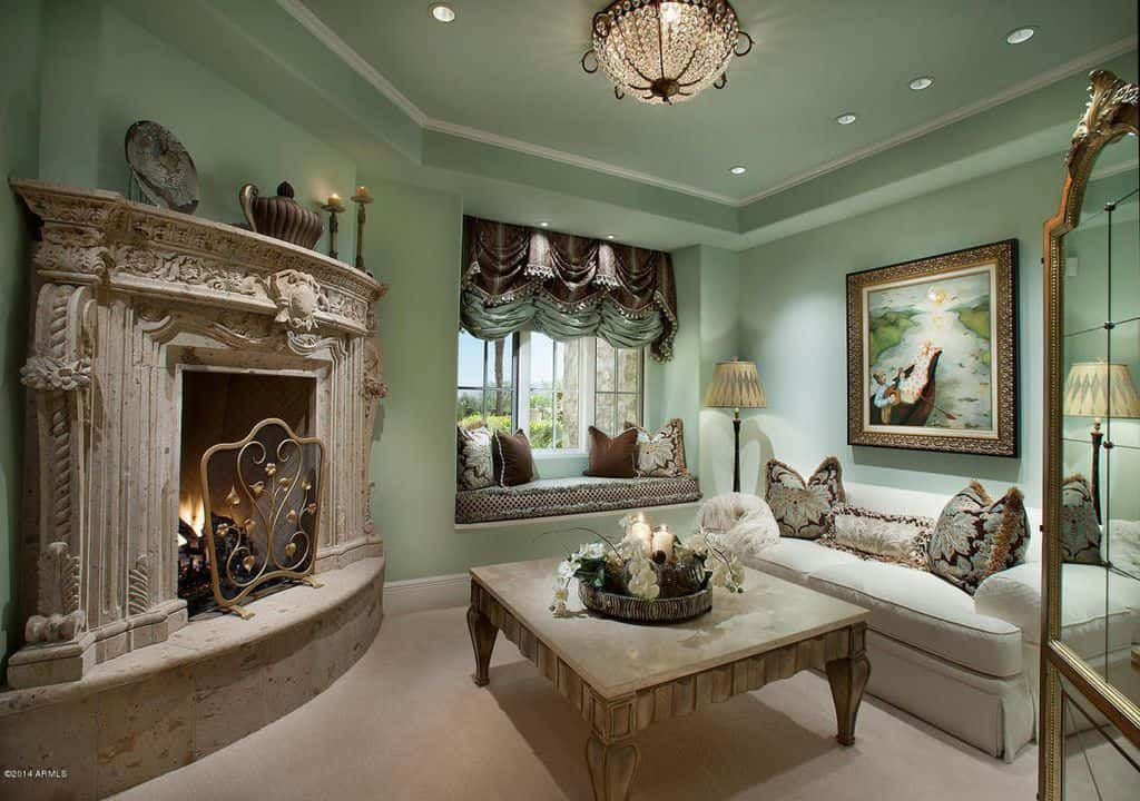 Mint green reading room with large fireplace and window nook seating.