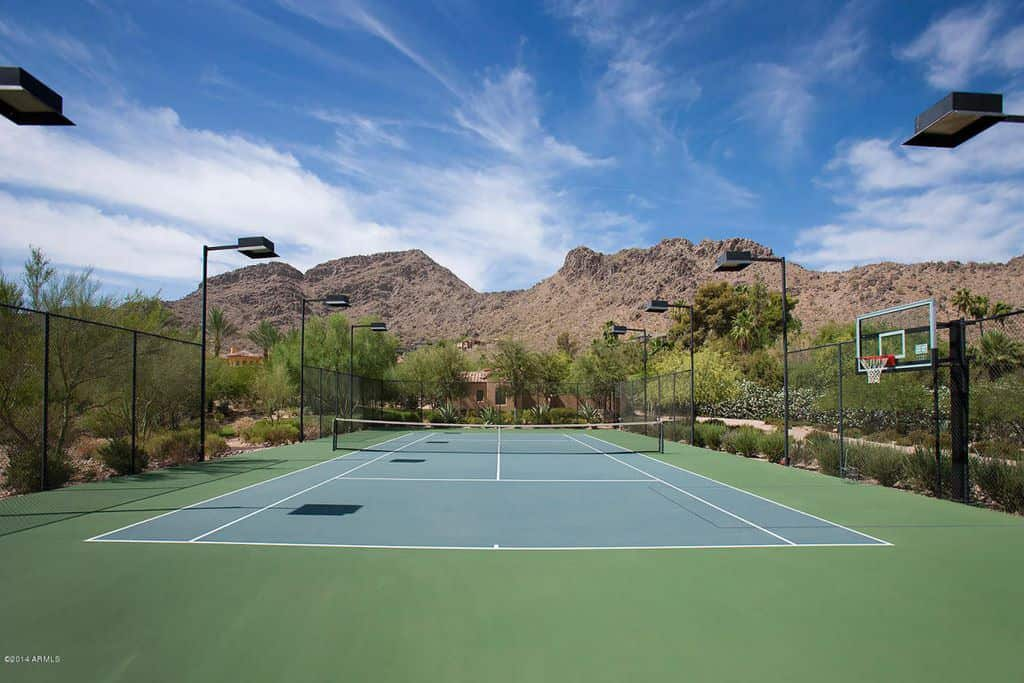 Backyard green and blue tennis court in the desert with lights.