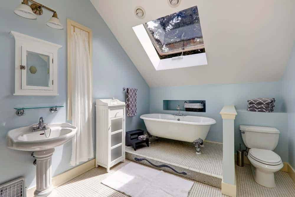 A stunning primary bathroom with a skylight above the freestanding tub set on the tiny tiles flooring. The pedestal sink looks elegant.