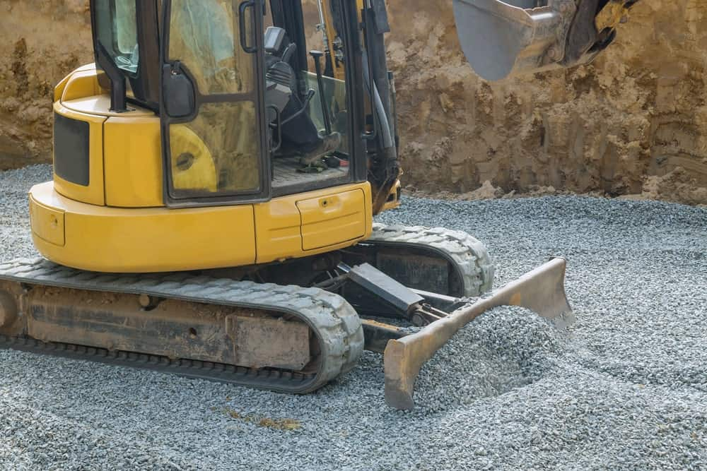 A construction vehicle laying gravel foundation.
