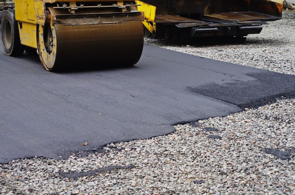 An asphalt driveway being flattened by a road roller.