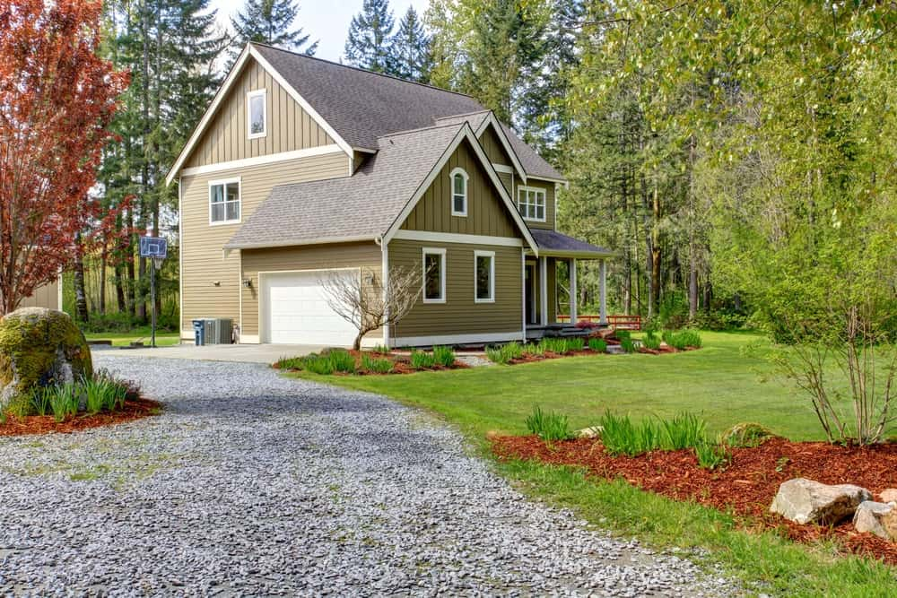 This is a graveled driveway leading to the house with green exterior walls surrounded by lush landscaping.