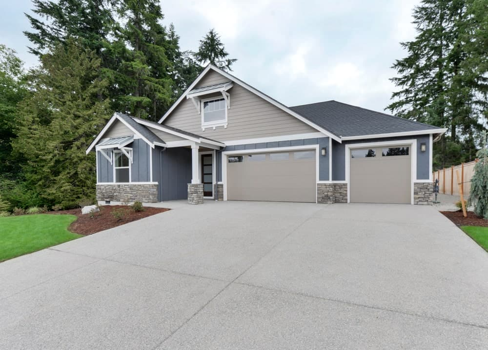 The gray exteriors of the house matches well with the concrete driveway.