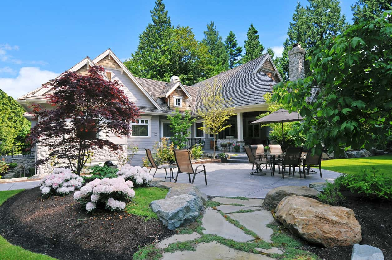 Luxurious patio in nicely gardened backyard with walkway extending off patio through the gardens.
