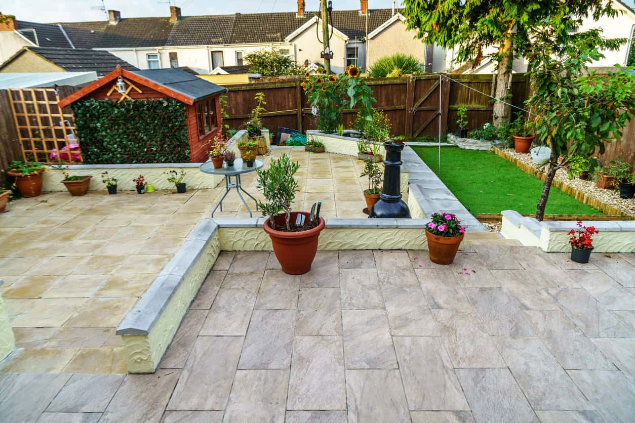 Large patio with brick tiles floors and an interesting lawn area on the side.