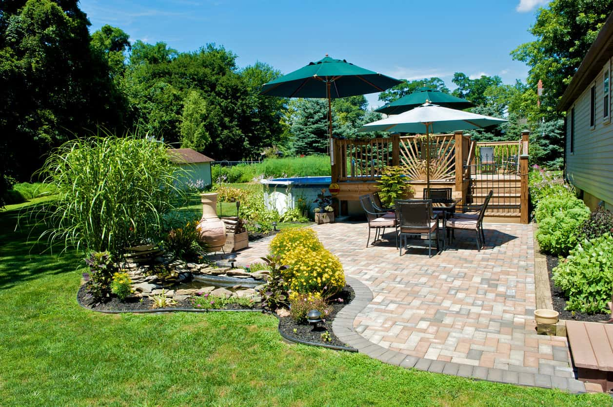 Large brick patio with plants and bushes on the perimeter.