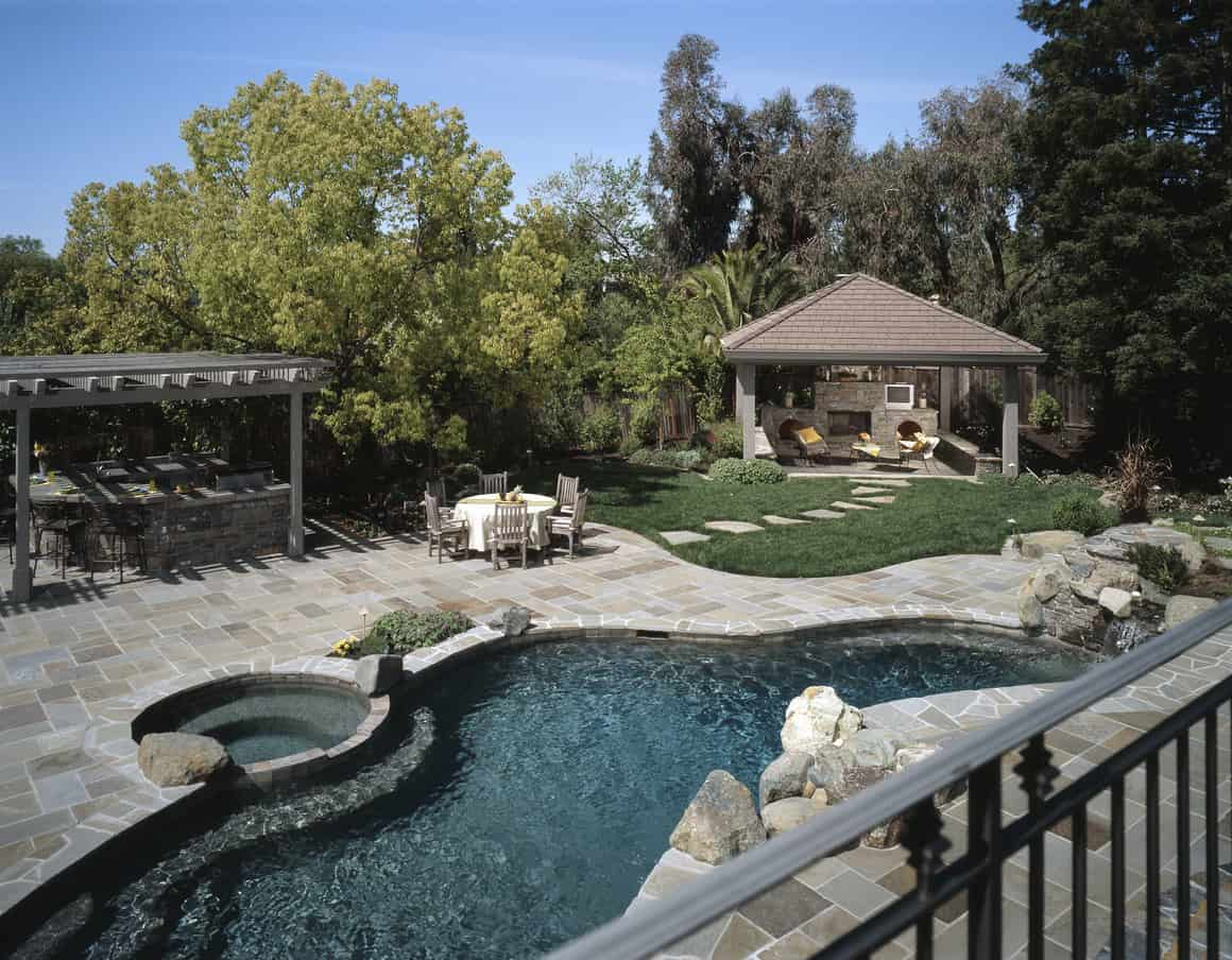 Gorgeous freeform swimming pool with gray stone patio in lovely backyard.