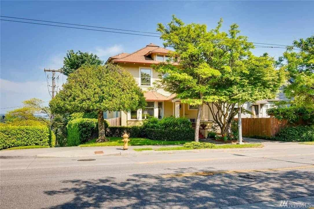 A beautifully restored craftsman home with a yellow exterior and a peaceful garden.