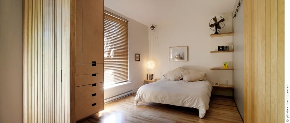 A master bedroom with hardwood floors and white walls. It also features built-in shelves.