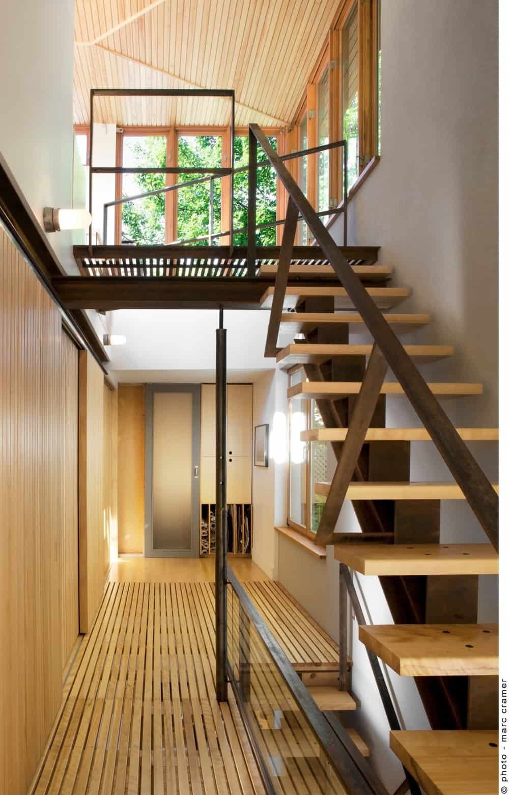 The hallway features hardwood flooring all the way to the staircase. Photo credit: Marc Cramer