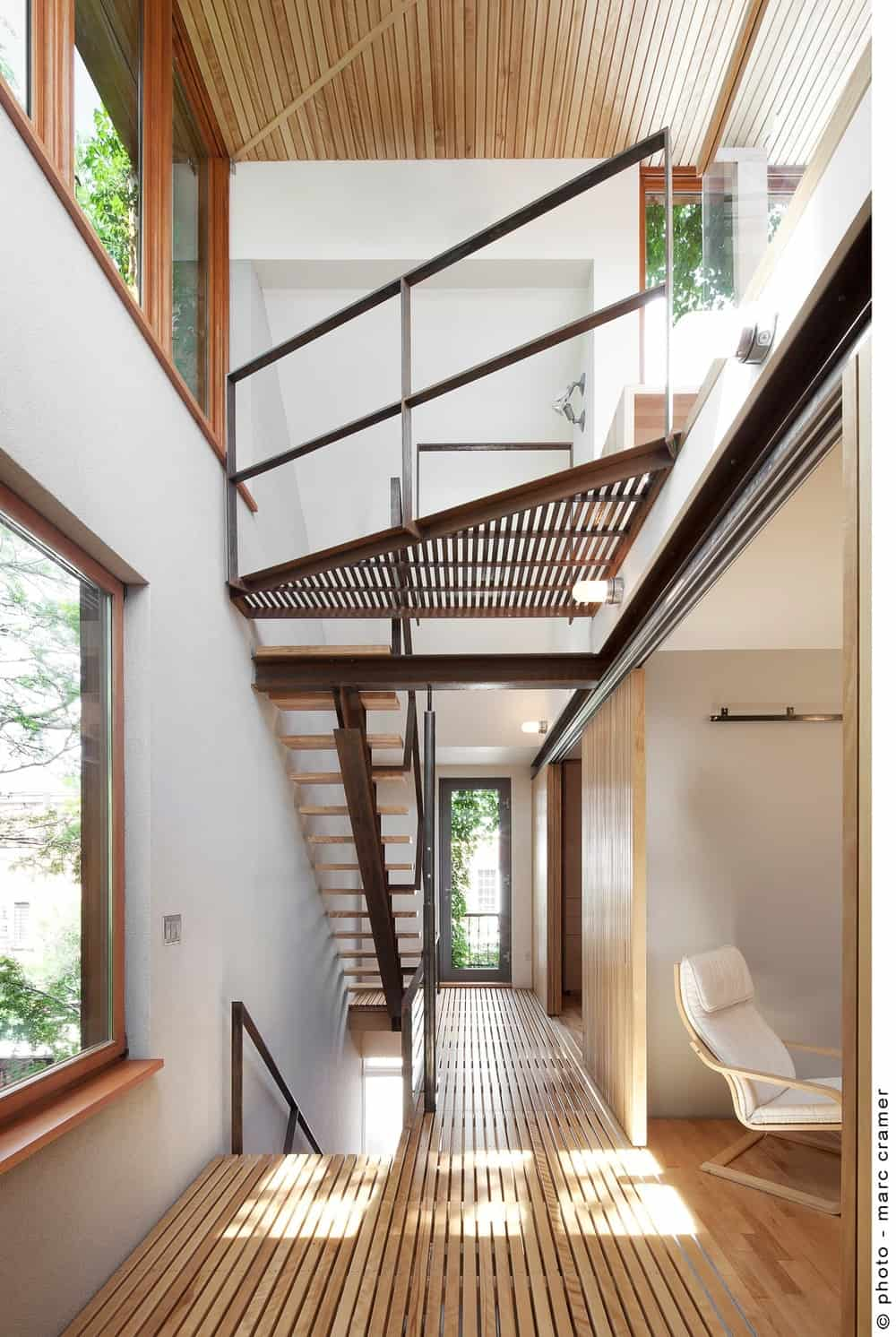 Another view of the hallway featuring hardwood flooring and white walls along with glass windows. Photo credit: Marc Cramer