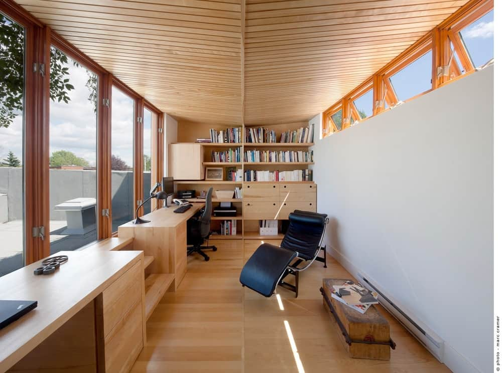 The home office features hardwood flooring and ceiling along with built-in shelves and glass windows and walls. Photo credit: Marc Cramer