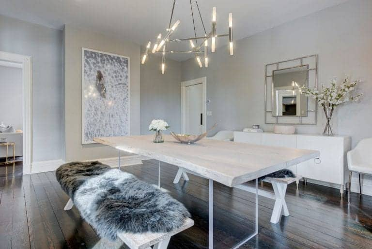 Stylish dining room designed with a wall art piece and framed mirror mounted above the white buffet table. It includes a light wood dining table paired with matching benches that are covered with gray faux fur blankets.