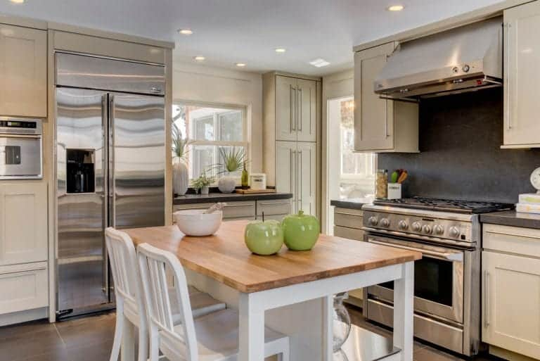 Off-white modern kitchen with stainless steel appliances and a white kitchen island with wooden surface and a pair of white chairs.