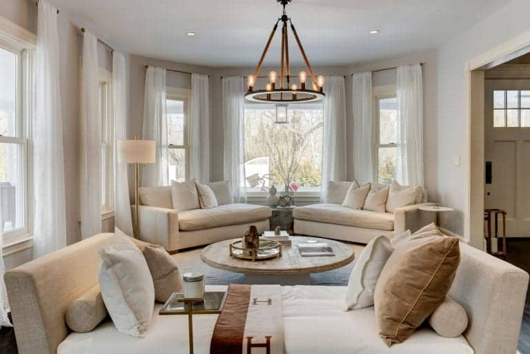 One of the living spaces offer comfortable seats lighted by a chandelier.