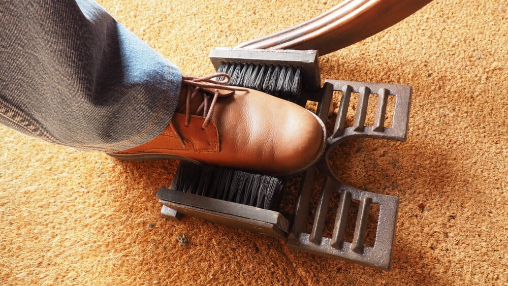 Traditional boot scraper made out of metal and synthetic bristles.