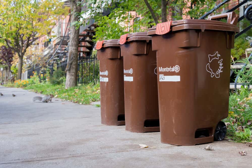 A set of three, brown composting bins for outdoor usage.