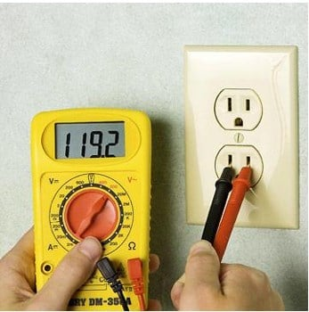 Inserting prongs of multimeter into outlet for testing the electrical outlet