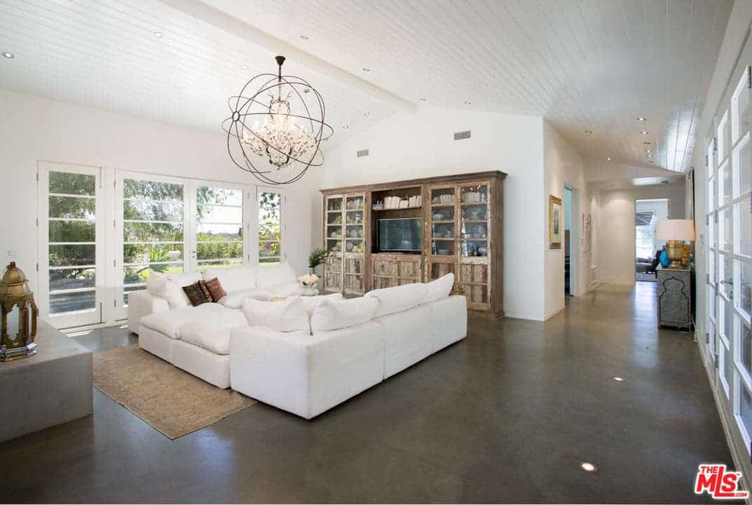 White living room illuminated by an oversized spherical chandelier that hung from the vaulted ceiling. It has concrete flooring and glass paneled windows overlooking the outdoor greenery.