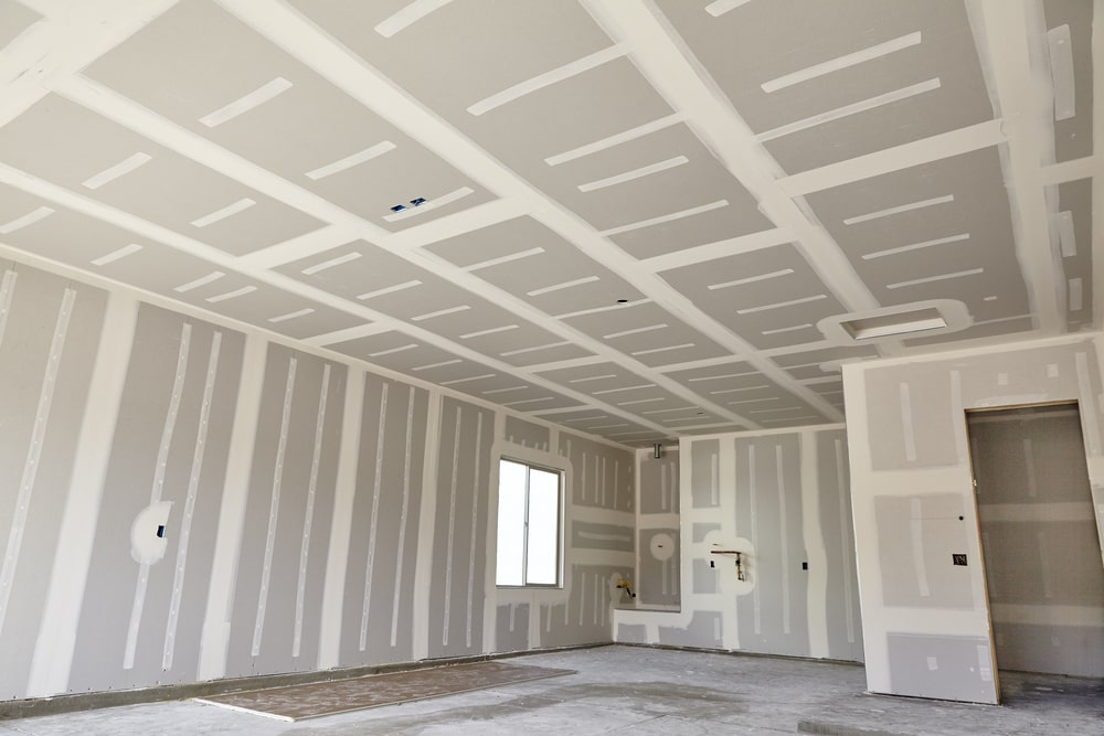 A large room under construction with drywalls.