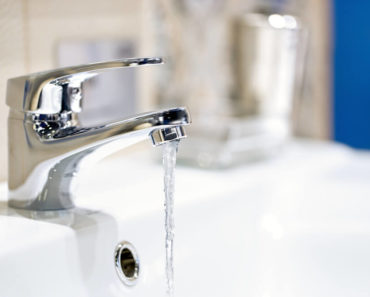 A close-up shot of a faucet with running water.