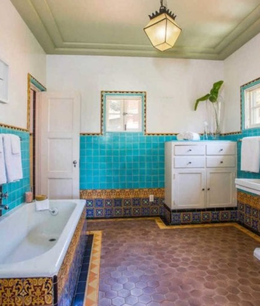 The bathroom features a tiles flooring and walls and has a drop-in tub along with a pedestal sink.