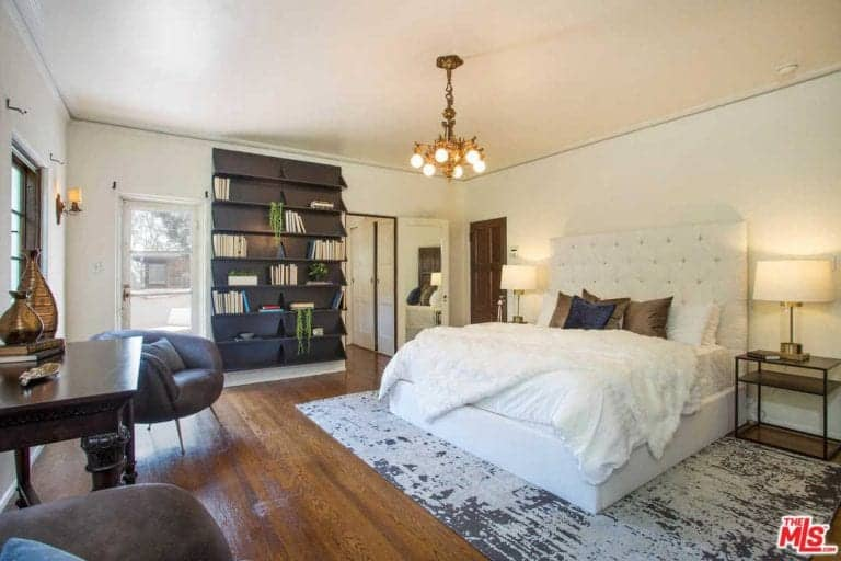 Primary bedroom featuring a large bed set on the rug covering the hardwood flooring lighted by two table lamps and a modish ceiling lighting, along with a large shelf on the wall.