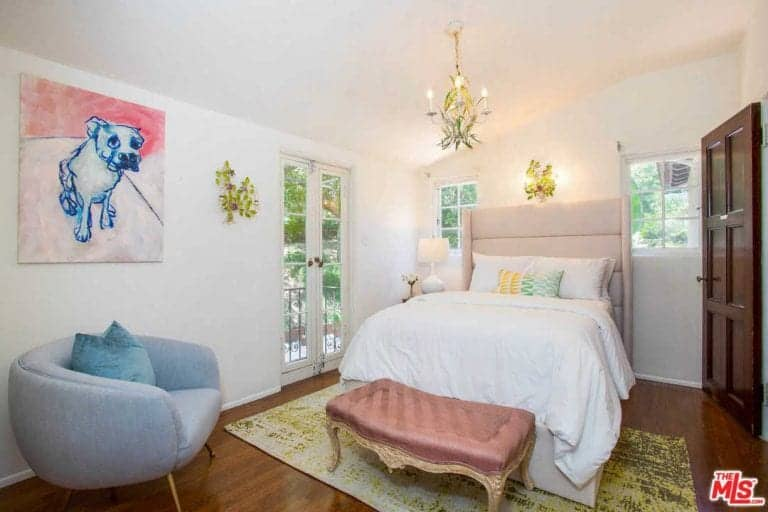 The kids bedroom boasts baby chandelier lighting along with hardwood flooring and a wall decor.