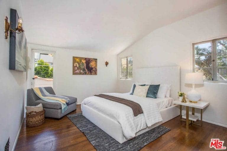 Another bedroom offers a hardwood flooring and a rug along with a comfortable sitting area.