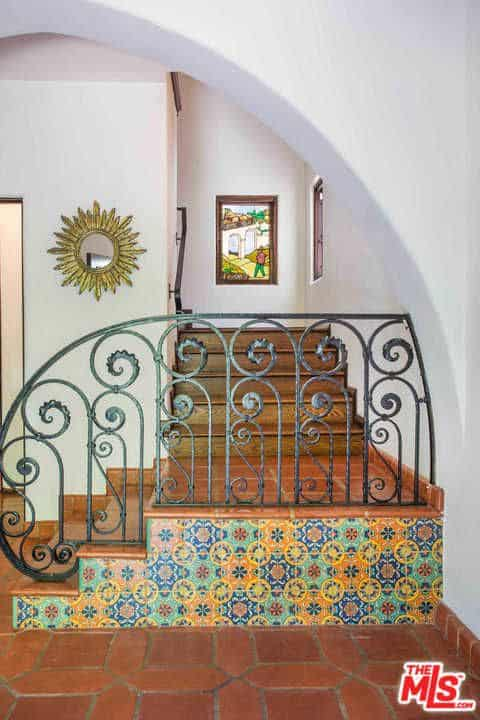 The home's staircase features elegant style that leads to various indoor amenities.