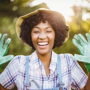 A woman happily showing off her garden gloves.
