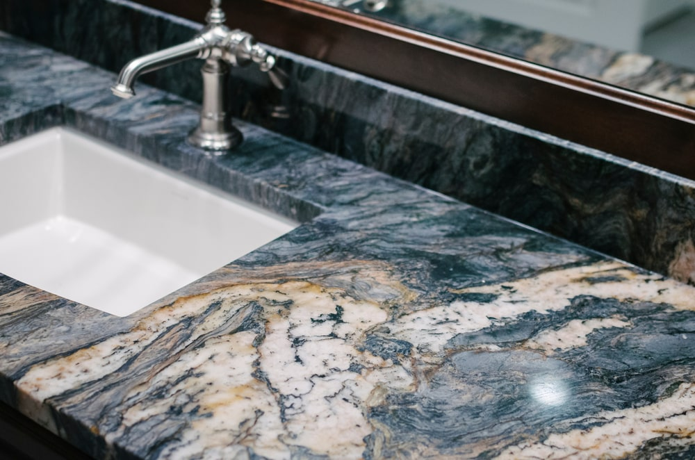 This is a close look at a bathroom sink area with granite countertops and backsplash.