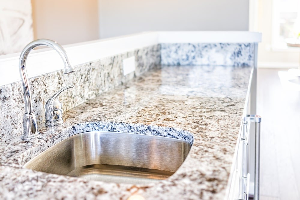 A kitchen sink with granite countertop and backsplash.